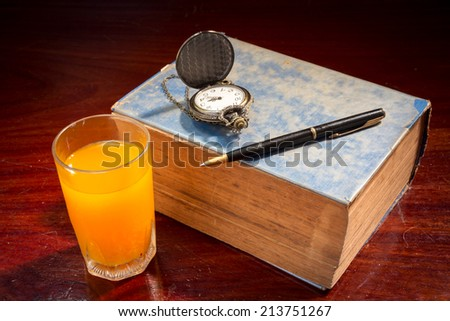 Still life book with pen,watch and orange juice.