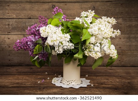 Still life. Bouquet of white and violet lilacs in a vase on a wooden table. Rustic style and selective focus. Toned. - stock photo