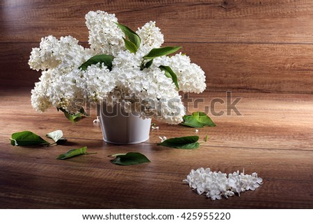 Still life. Bouquet of white lilacs in white a vase on a  wooden table ,Heart with petals. - stock photo