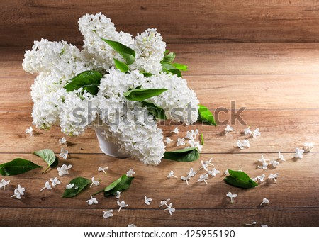 Still life. Bouquet of white lilacs in white a vase on a  wooden table Spilled with petals. - stock photo