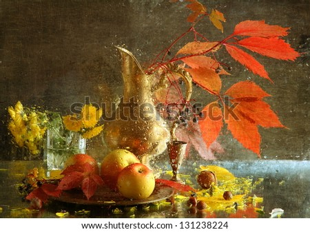 Still-life, branch with bright sheets in a graceful jug and juicy ripe appetizing apples