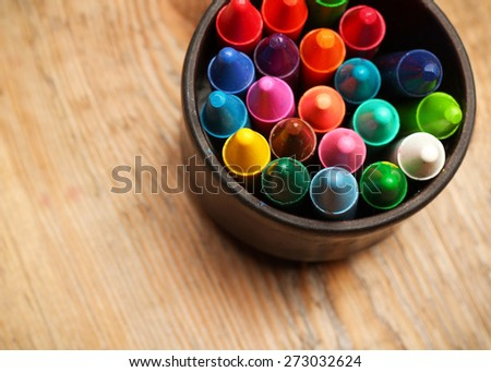 Still life, business, education concept. Crayons in a mug on a wooden table. Selective focus, top view - stock photo