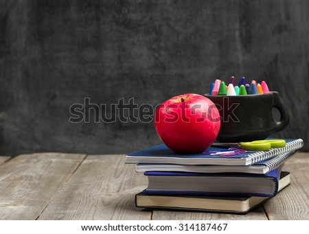Still life, business, education concept. Crayons (pencils) in a mug, notebooks and apple on a wooden table with chalkboard. Selective focus, copy space, school background