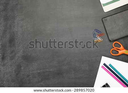 Still life, business, education concept. Office supplies, notepad, diary, marker, scissors and pencils on a chalkboard. Selective focus, copy space background, top view - stock photo
