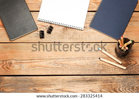 Still life, business, education concept. Office supplies, notepad, diary, staple and pencils on a wooden table. Selective focus, copy space background, top view - stock photo