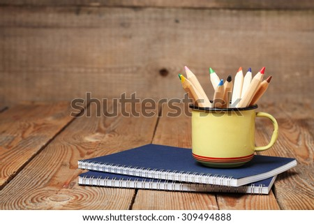 Still life, business, education concept. Pencils in a mug and notebook on a wooden table. Selective focus, copy space background - stock photo