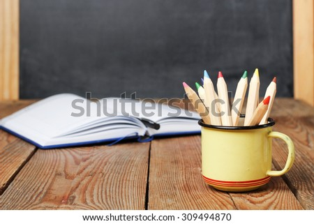 Still life, business, education concept. Pencils in a mug and open notebook on a wooden table with chalkboard. Selective focus, copy space, school background - stock photo