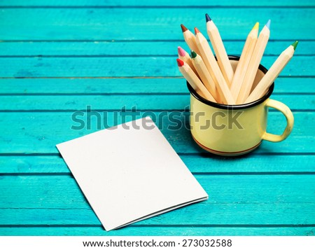 Still life, business, education concept. Pencils in a mug with notepad on a wooden table. Selective focus, copy space background - stock photo