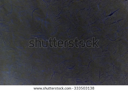 Still life close up detail of a rough, grungy and splashed piece of black paper with blue scratches and texture. Plain full frame background with cyan noise detail. Dark gray blank page backdrop. - stock photo