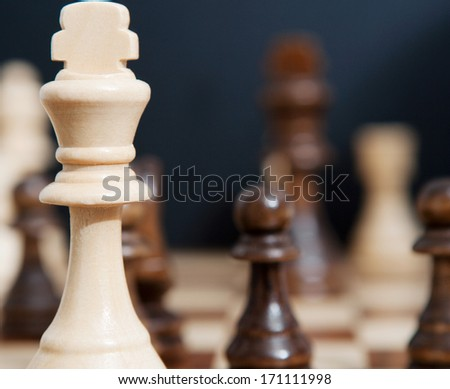Still life close up detail view of a king chess wooden piece on a chess board while a strategic game is being played. Professional game playing. - stock photo