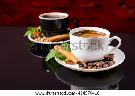Still Life Close Up of Black Coffee Served in Black and White Contrasting Cups with Saucers Garnished with Cinnamon Sticks, Fresh Mint and Coffee Beans on Shiny Black Reflective Surface - stock photo