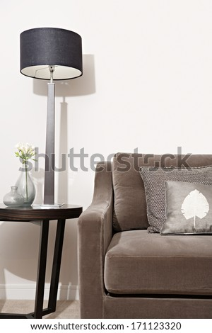 Still life close up view of an elegant brown sofa in a luxury home living room with different fabrics cushions and textures and a side table with a stylish lamp. Hotel interior suite detail. - stock photo