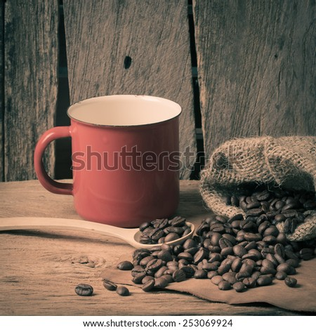 Still life, coffee bean on wooden table with red cup and wooden spoon - stock photo