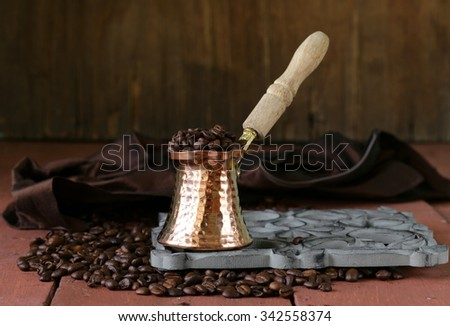 Still life coffee beans and coffee pot on a wooden table - stock photo