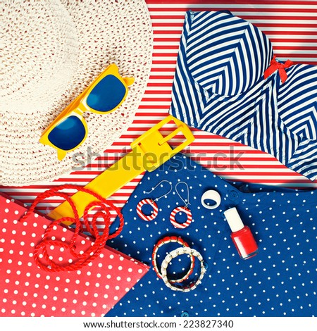 Still Life Collection of Womens Beach Themed Clothing on Striped Background - stock photo