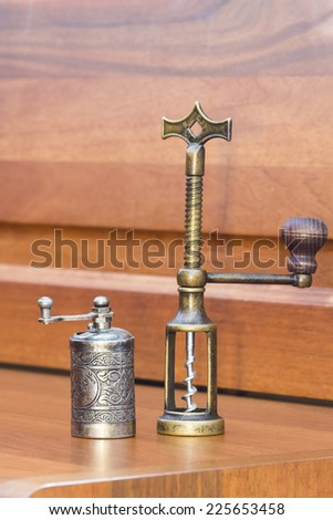 Still life composition with metallic pepper grinder and copper corkscrew on wooden table  - stock photo