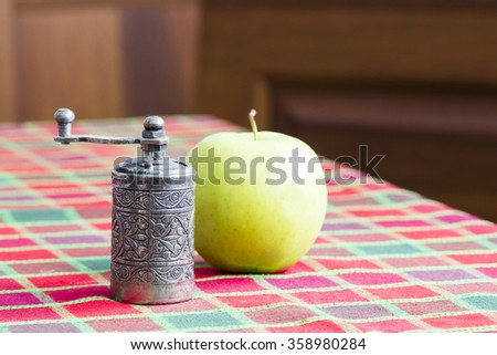 Still life composition with metallic pepper grinder and green apple - stock photo