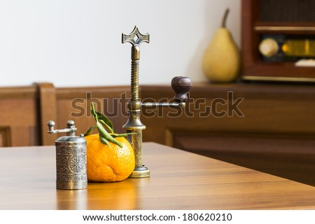 Still life composition with metallic pepper grinder, copper corkscrew and mandarin on colored table cloth  - stock photo