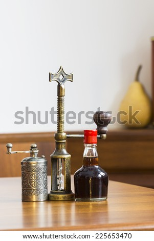 Still life composition with metallic pepper grinder, small bottle of aromatic vinegar and copper corkscrew on wooden table