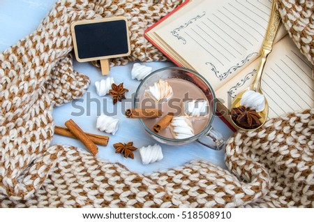 Still life cup of cocoa with marshmallow and star anise,cinnamon, notebook and warm scarf on the wooden board background.