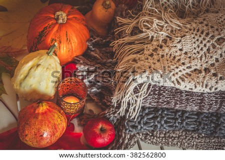 Still life decoration made with pumpkins, apples, pomegranate, woolen scarves and candle - stock photo