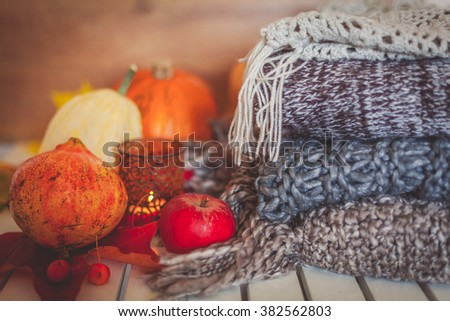 Still life decoration made with pumpkins, apples, pomegranate, woolen scarves and candle