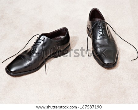 Still life detail of a pair of quality black leather business man shoes resting together on a luxury home carpet with space around them. Interior view with no people.