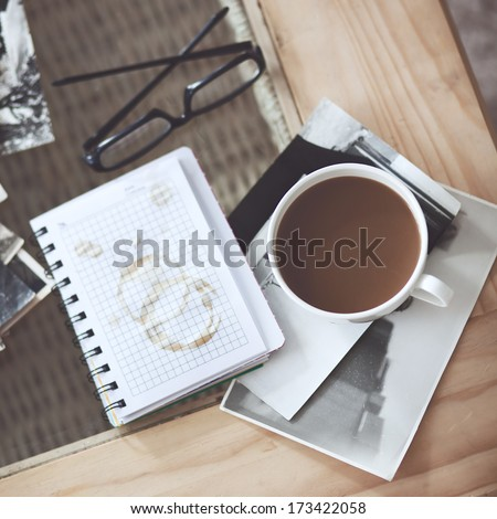 Still life details, cup of coffee and retro vintage black-and-white photos, top view point - stock photo