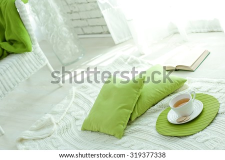 Still-life details of the interior, cup of tea and a book next to a cozy armchair white - stock photo