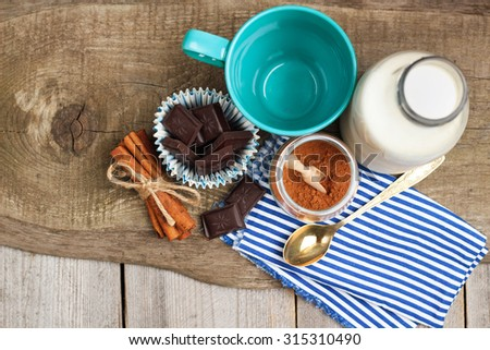 Still life, food and drink, christmas and holidays concept. Ingredients for homemade cacao (cocoa powder, milk, chocolate, cinnamon) on a wooden table. Selective focus, copy space, top view - stock photo