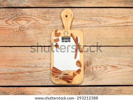 Still life, food and drink concept. Kitchen cooking utensils (cutting board, paper for recipe) on a wooden table. Selective focus, copy space background, top view - stock photo