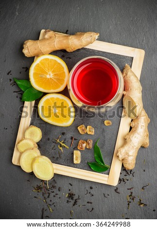 Still life, food and drink, healthcare concept. Ginger tea and ingredients on a black grunge stone table. Selective focus, top view - stock photo