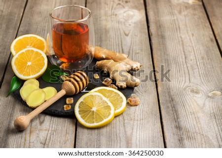 Still life, food and drink, healthcare concept. Ginger tea and ingredients on a black grunge stone table. Selective focus, copy space background - stock photo
