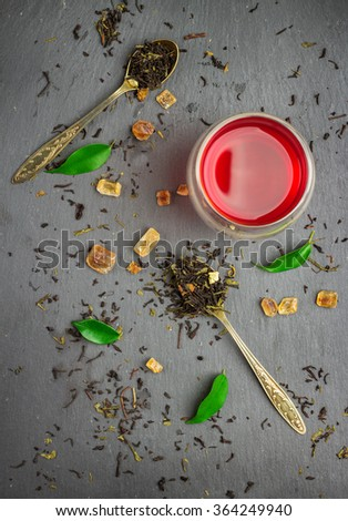 Still life, food and drink, healthcare concept. Glass of tea and ingredients on a black grunge stone table. Selective focus, top view - stock photo
