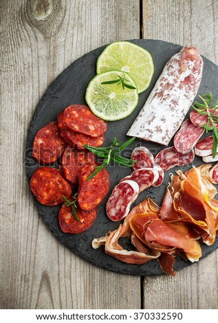 Still life, food and drink, holidays concept. Assortment of spanish tapas or italian antipasti, jamon, prosciutto, chorizo, salami on a grunge black board, rustic style. Selective focus, top view - stock photo