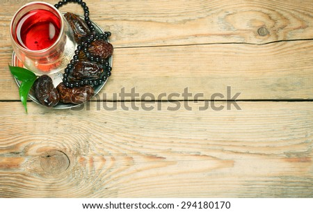 Still life, food and drink, holidays concept. Ramadan dates, tea and beads on a wooden table. Selective focus, copy space background, top view - stock photo