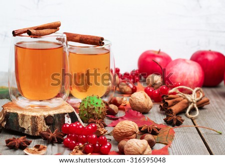 Still life, food and drink, seasonal and holidays concept. Autumn hot beverage in a glass with fruits and spices on a wooden background. Selective focus - stock photo