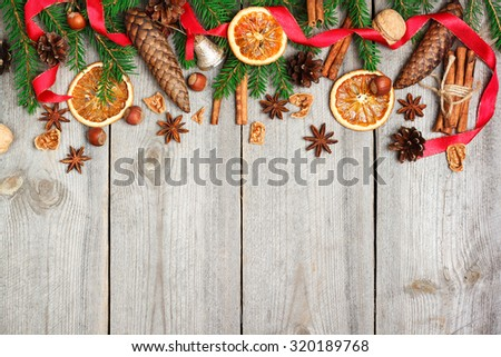 Still life, food and drink, seasonal and holidays concept. Christmas decoration with fir tree, oranges, cones, nuts, spices on a wooden table. Selective focus, copy space background, top view - stock photo