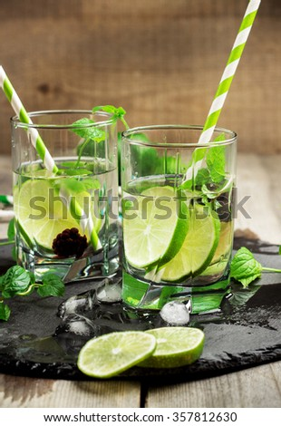 Still life, food and drink, seasonal and holidays concept. Mojito cocktail and ingredients on a grunge black table. Selective focus - stock photo