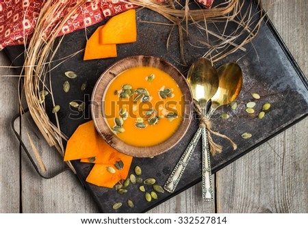 Still life, food and drink, seasonal concept. Fresh orange pumpkin soup in a bowl on a rustic table. Selective focus, top view - stock photo