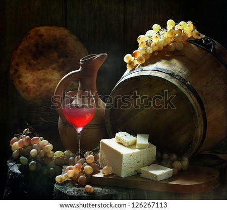 Still-life, fragrant pink wine a graceful glass with salty house cheese and ripe sweet grapes