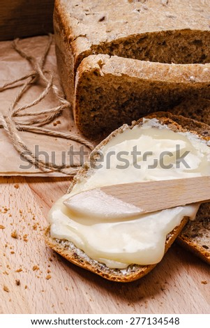 Still life fresh  whole wheat bread with butter and honey rustic wooden table background - stock photo