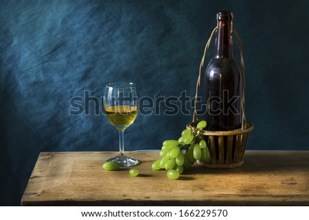 Still life fruit, Old red wine on wooden table and blue grunge background - stock photo