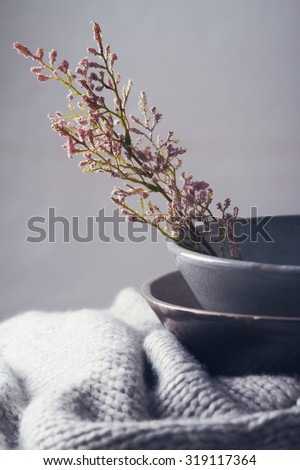 Still life gray vintage bowls with pink flowers and woolen scarf - stock photo