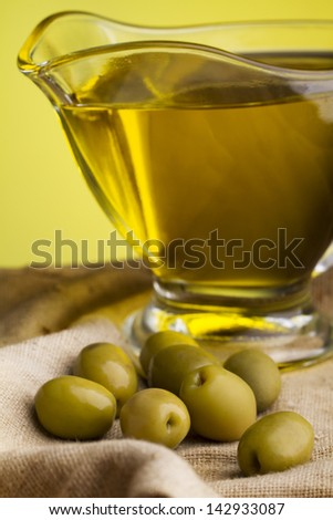Still Life- Green Olives And Olive Oil Against Yellow Background