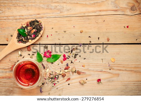 Still life, healthcare, food and drink concept. Herbal tea in a spoon and a glass on a wooden table. Selective focus, copy space background, top view - stock photo