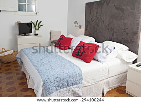 Still life home interior view of a double bed in bedroom in a stylish home with cushions and pillows, indoors. Design hotel room with a luxury headboard and furnishings, aspirational lifestyle. - stock photo