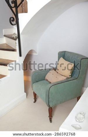 Still life home interior view of a traditional quality and luxurious wooden armchair in a living room with stairs, indoors. Elegant reading room with upholstery chair, empty space. - stock photo