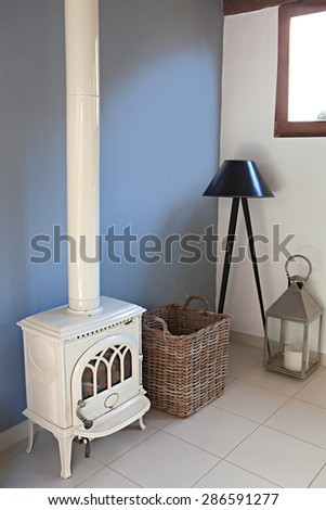 Still life home interior view of a traditional quality wrought iron fireplace stove in a stylish home living room, indoors. Elegant stylish standing lamp, empty space, aspirational lifestyle.