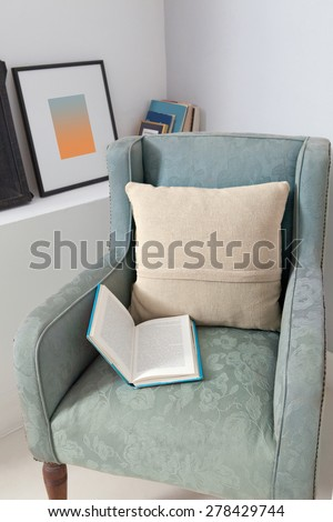 Still life home interior view of an elegant armchair in a stylish home with cushions and an open book laying on the chair, indoors. Reading room with picture frames and book, aspirational lifestyle. - stock photo
